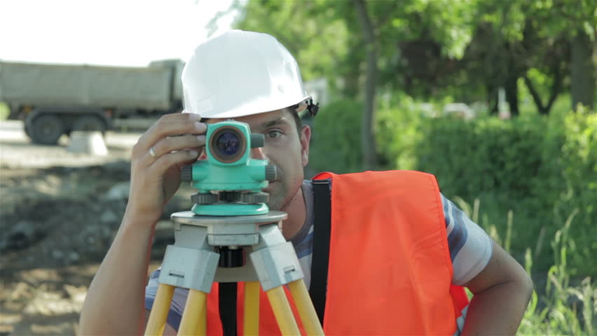 Portrait of surveyor during measures the distance at road construction. Close up. Land surveyor taking levels with modern equipment. Land surveyor measuring distance at road construction. Roadwork.