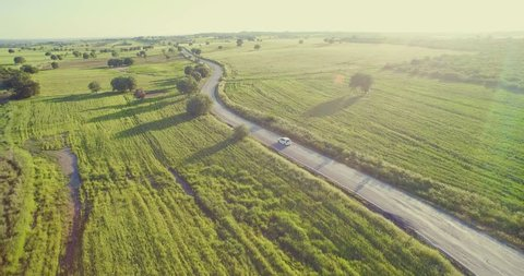4K aerial footage of a car riding on a road between green fields in the sun set.