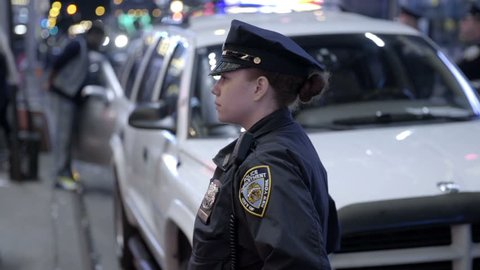NEW YORK - APRIL 26, 2015: attractive female police officer in uniform at night in slow motion, Times Square, NY. The NYPD enforces the law in the 5 boroughs of NYC, USA.