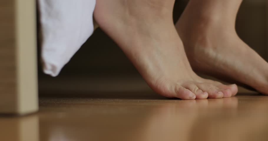 Feet step to toes from morning bed touching floor with dust macro close up 4k. Woman wakes up gets out of bed on tiptoes in bedroom with white blanket corner falling at background