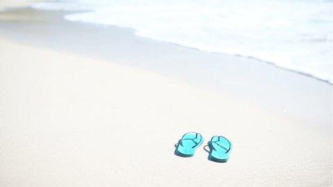 Flip flops on a sandy ocean beach