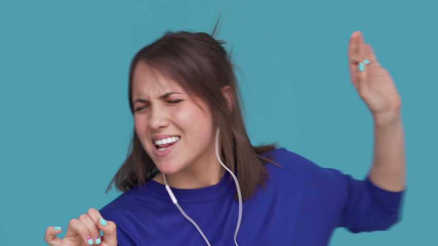 Portrait of glad pleased woman listening her favourite song on smartphone dancing and singing while enjoying music with headphones over blue background closeup. Concept of emotions