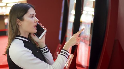 Teenager buying movie ticket from vending machine at movie theater at mall. Woman using cellphone talking to friend discussing which film to choose