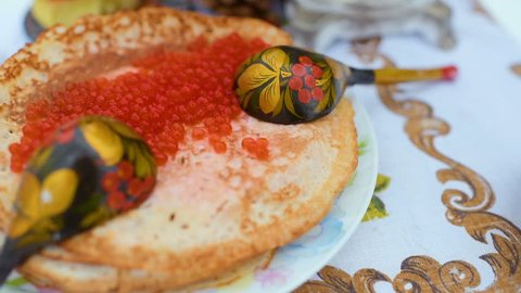 pancakes with red caviar close-up on the background of the festive table. Celebration of carnival in Russia. Maslenitsa, Shrovetide