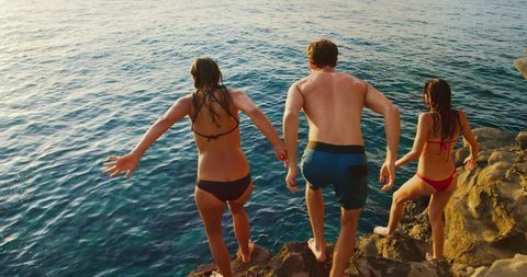 Friends cliff jumping into the ocean at sunset