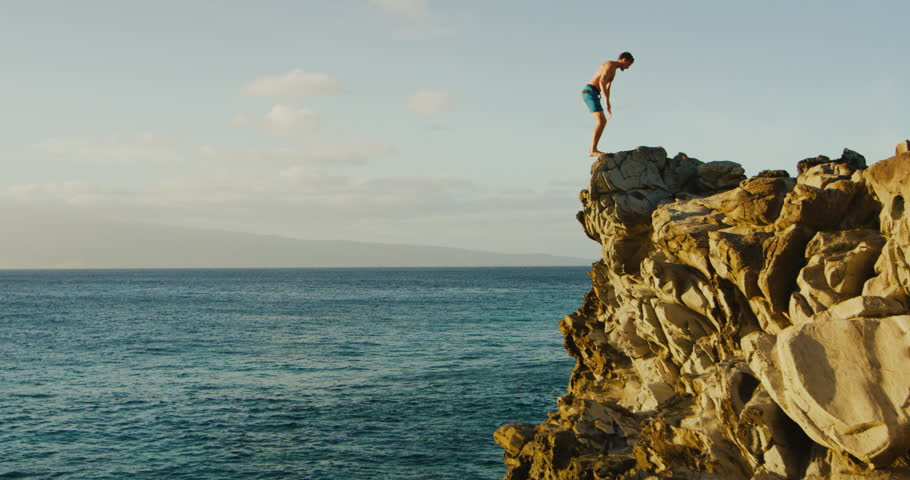 Young man doing backflip cliff jumping into ocean at sunset #1006626115
