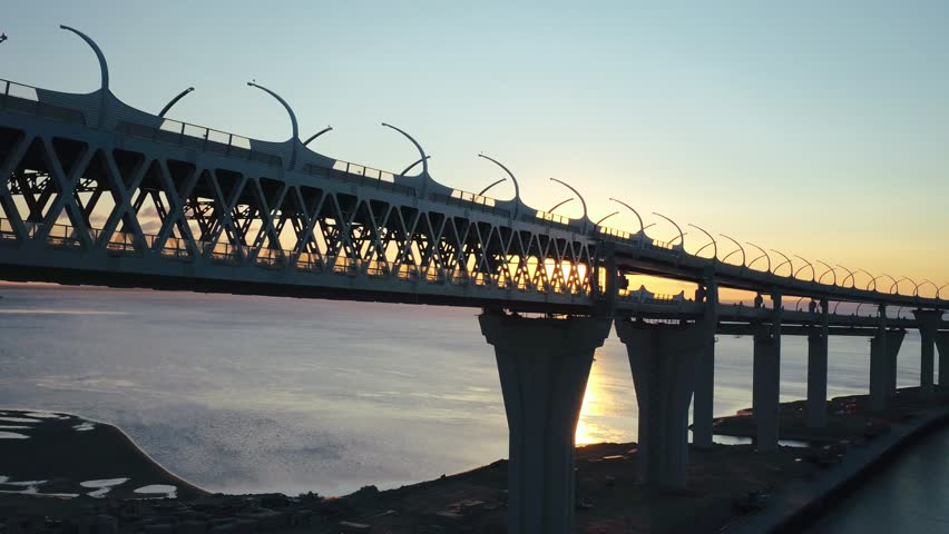 Car driving on modern multilevel highway bridge on background evening sunset