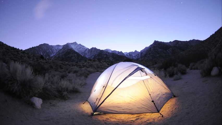 CIRCA 2010s - Dolly shot of a tent and star trail time lapse below Mount Whitney in the Sierra Nevada Mountains near Lone Pine, California.