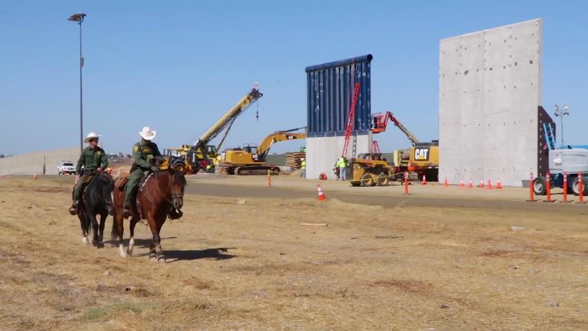 CIRCA 2010s - Horsemen from the US Border Patrol ride beside Trump border wall prototypes along the U.S. Mexico border.