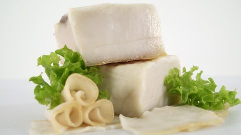 Dolly: Sliced processed meat products on white background. Salted lard with slices and herbs closeup.