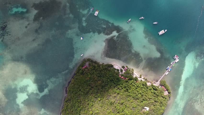 Aerial drone shot during sunny afternoon. View from top of a beautiful island surrounded by reef, clouds shadow. Located in Martinique Ilet Madame. Filmed with a phantom4
