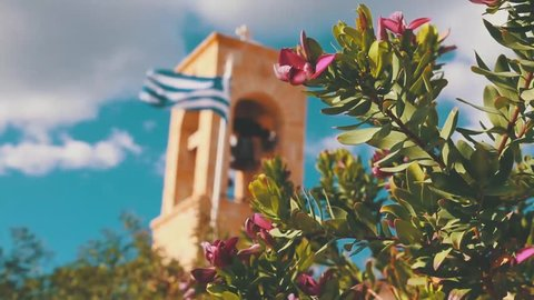 Greek church bell and flag in the wind on a sunny day, blooming pink flowers on foreground