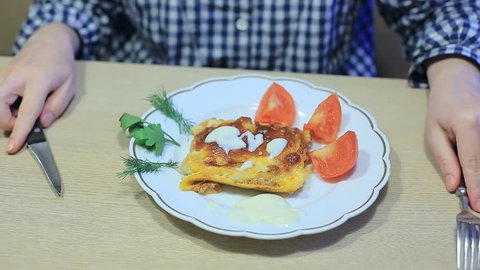 A housewife eats lasagne cooked at home. homemade food