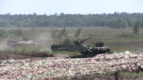 KHARKIV, UKRAINE - CIRCA AUGUST 2016: Ukrainian military trains on military field. War in Ukraine in Donbass. Heavy armored army tank shoots on battle field