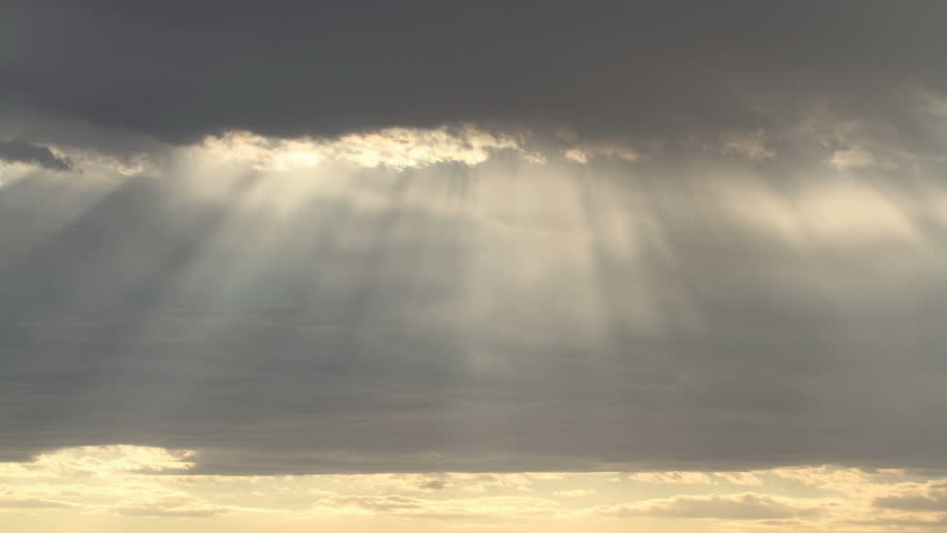 Time lapse of dramatic rain clouds and rays of sunlight