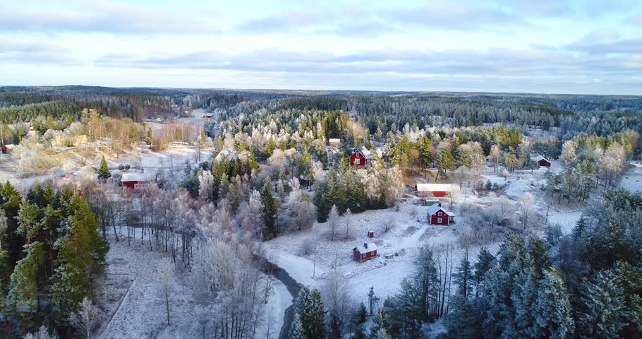 Frosty town, Cinema 4k aerial backward view over a frozen village, in a a snowy forest, on a sunny winter day, in Uusimaa, Finland
