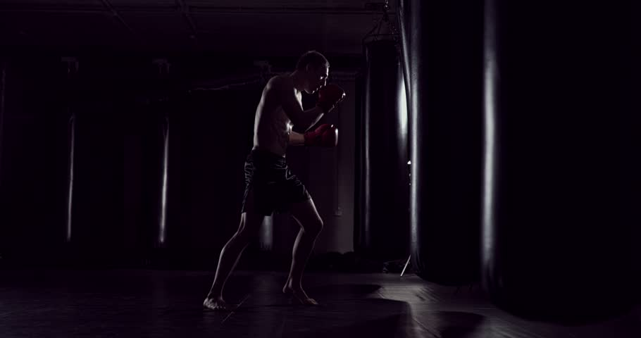 Boxer punching bag. Slow motion sequence. Strong athlete hits a punching bag. Kickboxing men training punching bag in fitness studio. Fighter Training Slow Motion | Shutterstock HD Video #1006718695