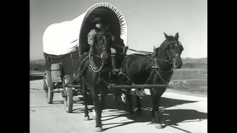 CIRCA 1930s - A man rides in a covered wagon as he steers the horses that are pulling it in the 1930's.