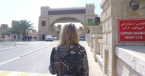 DUBAI, UAE – MARCH 2016 : Video shot of blonde woman walking towards Jumeirah Mosque on a sunny day