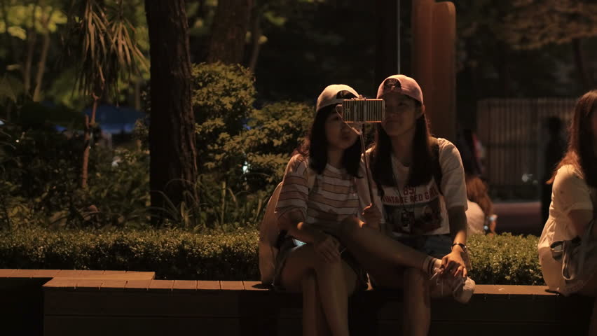 SEOUL, SOUTH KOREA – JULY 216 : Video shot of local girls taking selfies at night in public park | Shutterstock HD Video #1006794715