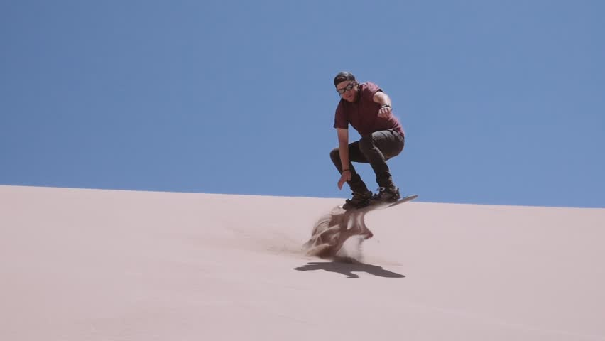 Man making tricks  with a sandboard at the Sand Dunes of the Dead Valley, Atacama desert. Slow motion