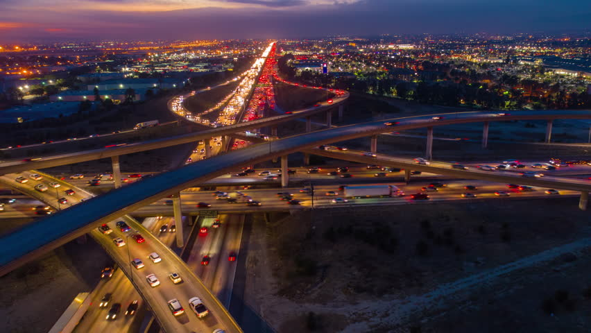 Urban aerial drone time lapse in motion or hyperlapse at night flying along an interstate with traffic showing the on and off ramp circles.