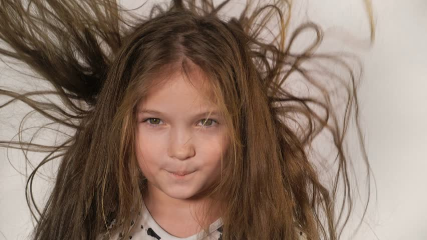 Happy little girl in the studio on a gray background. She jumps, shows different emotions. Hair fluttering from the wind. Super slow motion, shot at 180fps. | Shutterstock HD Video #1006832515