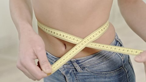 Crop woman measuring waistline