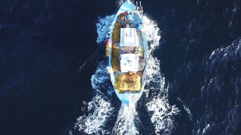 Aerial drone bird's eye view video of traditional fishing boat cruising in deep blue clear waters