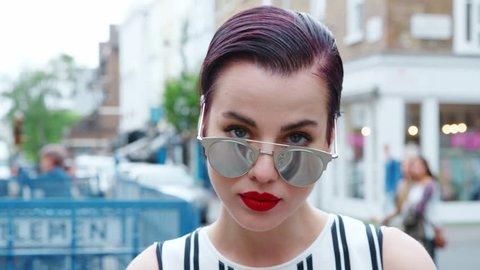 Stylish Woman Wearing Sunglasses Standing Outside City Building