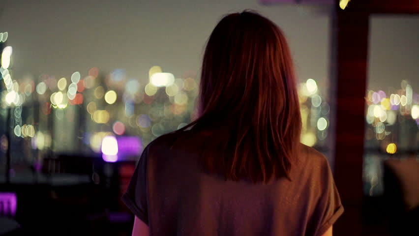 Young woman walking on terrace and admire city view during night  | Shutterstock HD Video #1006924975