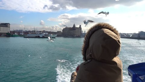 Kadikoy, Istanbul, Turkey - 15th of January 2018: 4K Woman feeds seagulls with bread from the moving boat at the sunny winter day