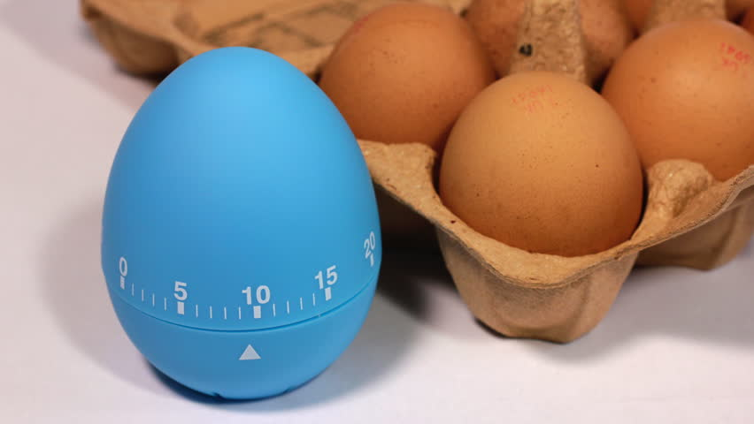 Kitchen egg timer countdown to zero time lapse with a pack of eggs.