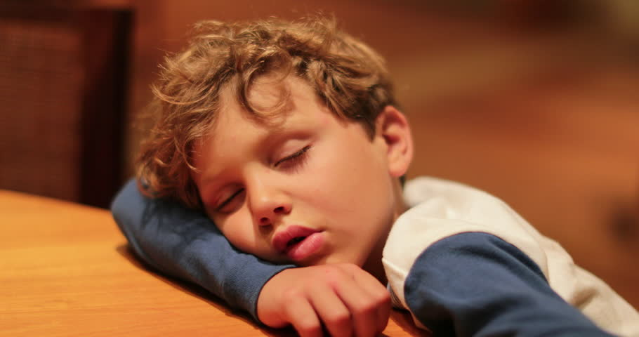 Drooling sleepy 7 year old child fell asleep on desk. Drained young boy resting after a long day of activities. Expressive candid authentic real life moment of child sleeping