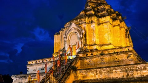Chiang Mai, Thailand. Illuminated Chedi Luang Pagoda at Wat Chedi Luang Temple with cloudy sky at sunset. Popular landmark in Chiang mai, Thailand. Time-lapse at night, zoom in