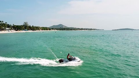 Man riding on a jet ski. Aerial view man driving a jet-ski at sea. Jet ski on the water of the sea. Man riding a water bike jetski. Travel concept. People are playing a jet ski in the sea. Top view.