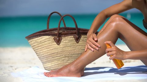 Woman applying sunscreen suntan lotion on legs at beach after taking tanning oil spray bottle from beach bag. Young lady is sunbathing at beach. Female in bikini is relaxing during summer vacation.