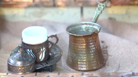 Making turkish coffee in copper cezve over hot sand. Milling of grains. On the hot sand Turk with a running coffee. Running coffee close up. hot sand with burning fire. A cup of coffee.
