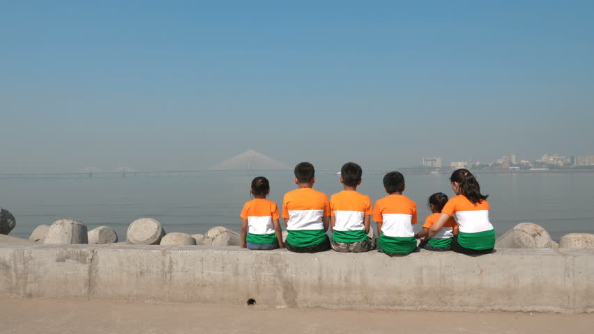 A group of children wearing Indian flag tricolor t-shirts sitting on a platform against Bandra worli sealink built over Arabian sea, Mumbai, India