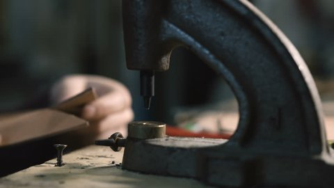 Leather craftsman making an handmade genuine leather bag. Close up of his hands using an hand rivet press in order to puncture leather 1