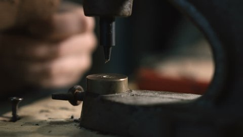 Leather craftsman making an handmade genuine leather bag. Close up of his hands using an hand rivet press in order to puncture leather 3