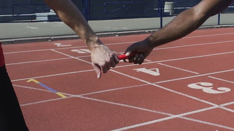 Closeup view of participant handing off baton to next runner, world championship