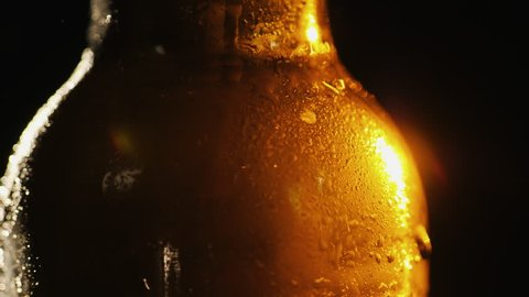 A bottle of cold beer on a black background. A ray of light beautifully illuminates it, it slowly rotates