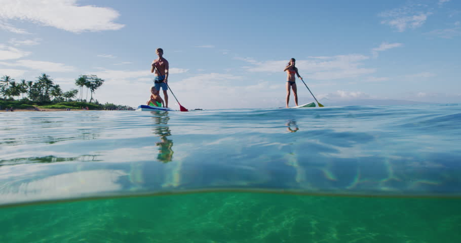 Family stand up paddle boarding in the ocean, active lifestyle