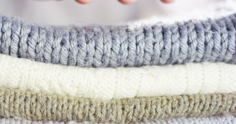 A hand touching a pile of colorful wool sweaters warm fluffy soft and comfortable to wear. cleaning concept, softness, warmth, cashmere, whiteness.   Shutterstock HD Video #1007045125