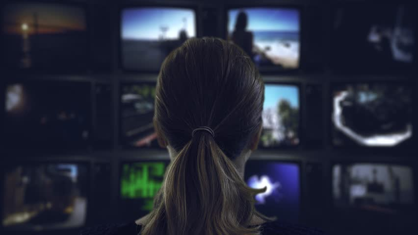 Watching Tv Television Broadcast. Head shot of a ponytail woman watching many videos in a wall of televisions | Shutterstock HD Video #1007045725
