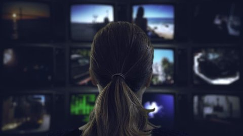 Watching Tv Television Broadcast. Head shot of a ponytail woman watching many videos in a wall of televisions