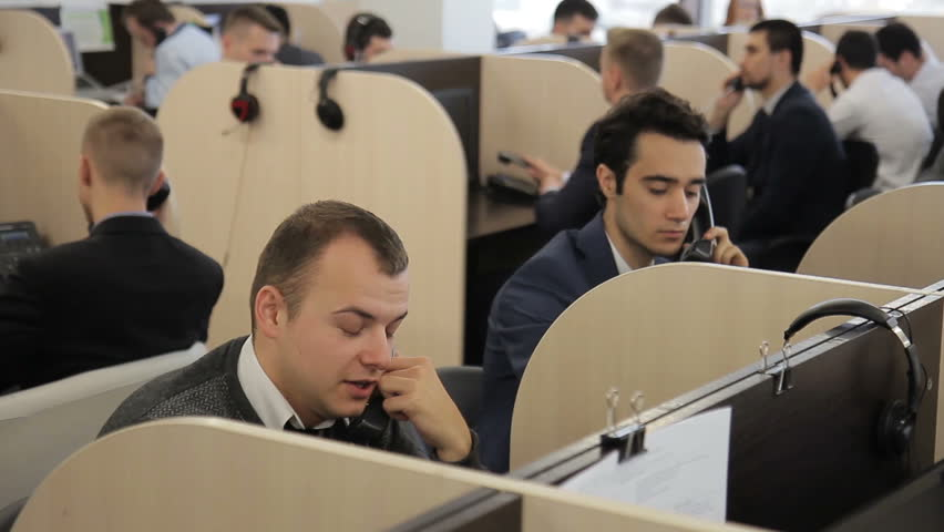 Male employees talk on phone in call center of company. Young people speak actively with customers, sitting on individual workstations separated by partitions. Promising specialists dressed in style