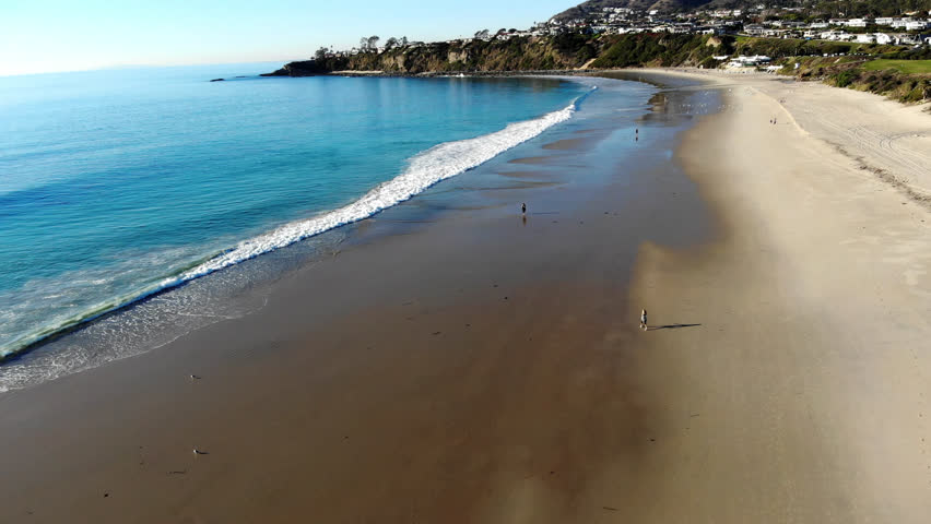 Aerial Drone Shot Flying from the Sandy Beach out to the Waves and Crystal Clear Water, with Cliffs in the Distance at Salt Creek Beach in Laguna, Orange County, California.