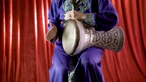 A female Arabic percussionist playing the rhythm beladi on a decorated clay doumbek with fish skin head.